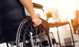 Closeup of wheelchair wheel and user's arm