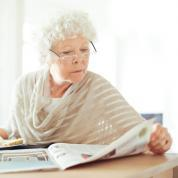 Older woman reading about NTI in her local newspaper.